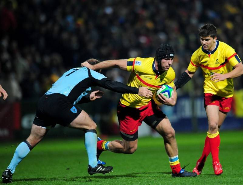 Romania's Tonita Ovidiu (C) fights for the ball with Coral Alejo (L) of Uruguay during the 2011 World Cup qualifier second leg rugby match, in Bucharest on November 27, 2010. Romania won 61-33. AFP PHOTO DANIEL MIHAILESCU